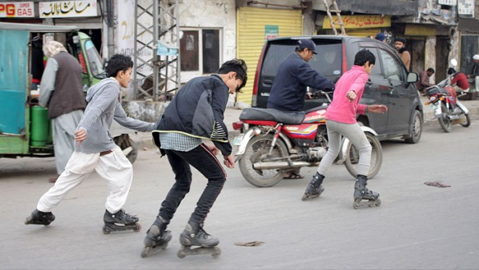Youngsters enjoying Roller skating on a busy road which is a sport traveling on surfaces with roller skates. It is a recreational activity