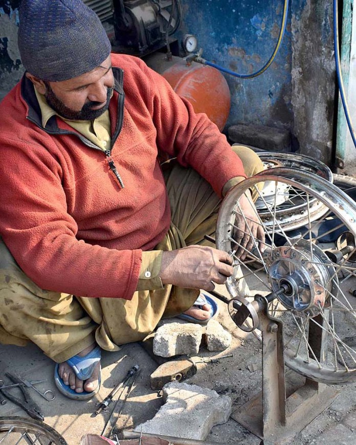 A skilled labourer repairing motorcycle wheel at his work place