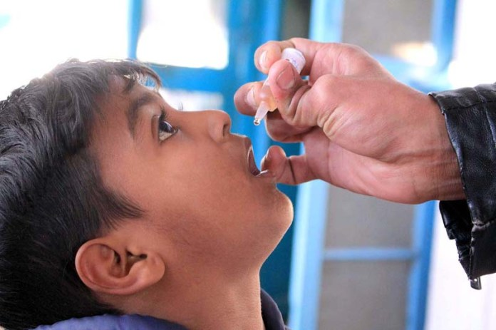 Health worker administering polio drops during 5 days anti polio campaign in the city