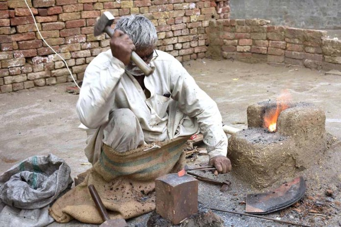 A blacksmith is busy in his routine work at his workplace