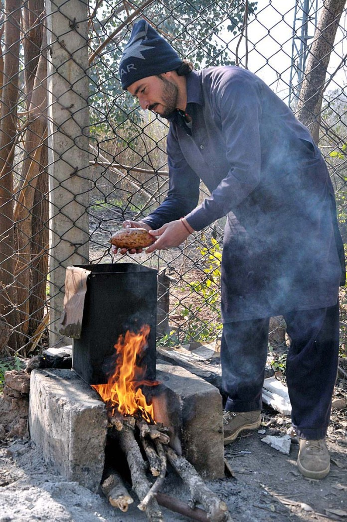 A vendor roasting sweet potatoes at his roadside setup in Federal Capital