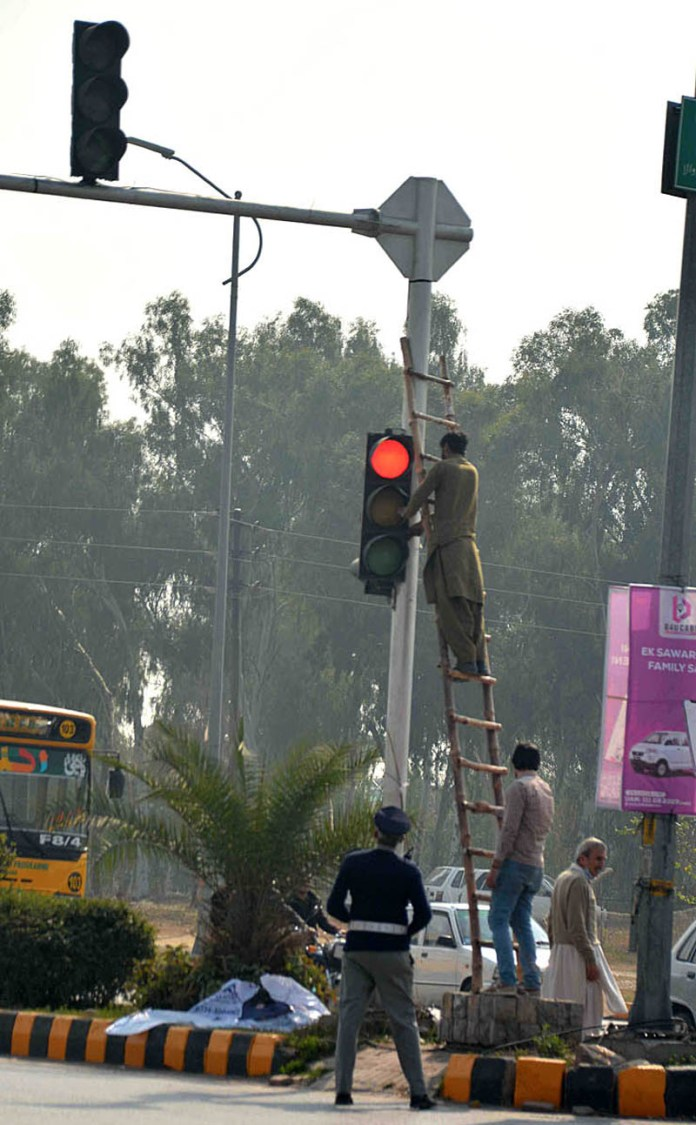 February 11 - Electricians repairing the signal lights at 9th Avenue during maintenance work in the city