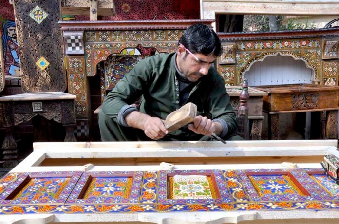 An artisan busy in curving work on wooden furniture at Lok Virsa