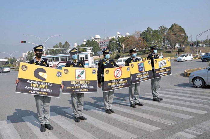 Traffic police officials holding placards during awareness campaign for commuters about traffic rules