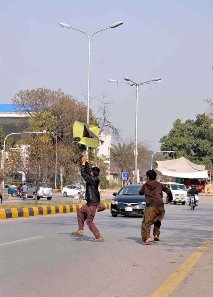 Youngsters catching a kite on the road in Federal Capital