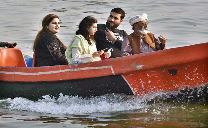 A family enjoying a ride on boat in Rawal Lake