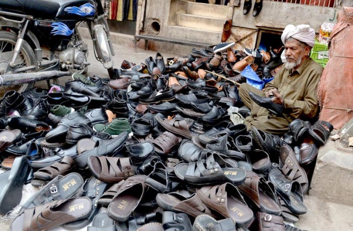 An elderly man repairs and sells old shoes at Lenda Bazaar