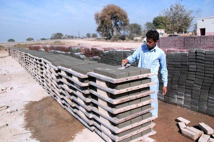 A worker busy in making cement blocks at his workplace