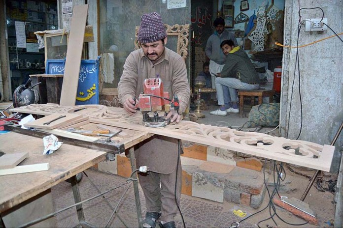 A worker busy in carving design on wooden sheet at his workplace