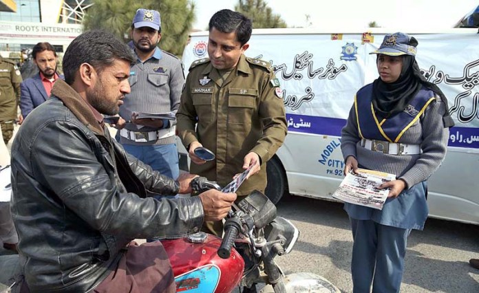 Chief Traffic Officer (CTO) Mazhar Iqbal distributing awareness pamphlets among the motorcyclists during awareness campaign in the city