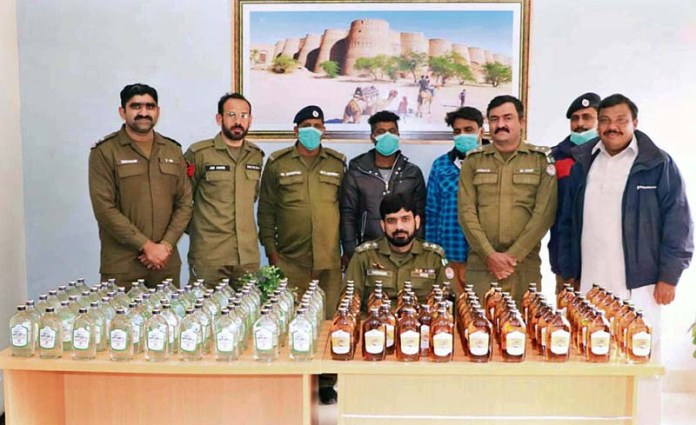 Police officials Baghdod al-Jadeed station displaying seized 170 bottles of liquor before the media persons