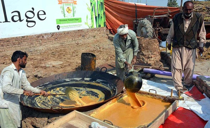 Farmers preparing traditional sweet stuff (Gurr) through extracted sugarcane juices