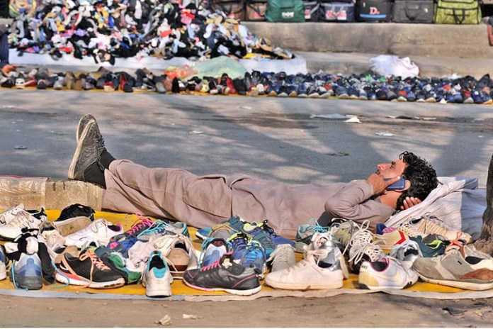 A vendor talking on his cell phone while displaying old footwear to attract the customers
