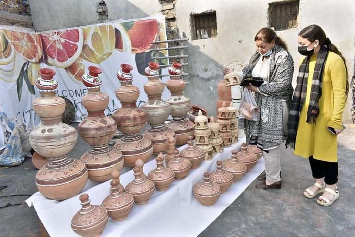 Women taking keen interest in clay pots displayed on stall during Kitchen Garden Festival Pakistan