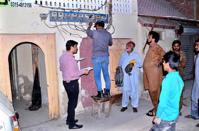 HESCO staffers disconnecting the illegal lines of electricity at Latifabad