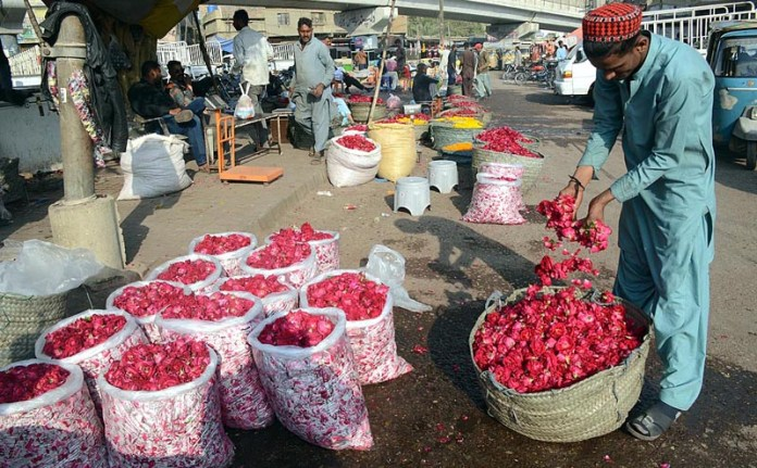 A vendor displaying and arranging roses to attract customers outside his shop in Flowers Market