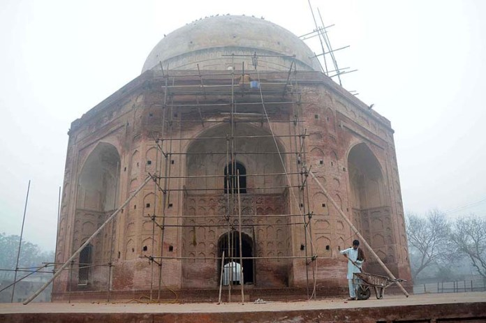 Labourers busy in renovation work on the main gate of historical shrine of Khan Bahadur Khan