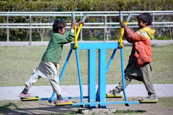 Gypsy children enjoying swing in a local park