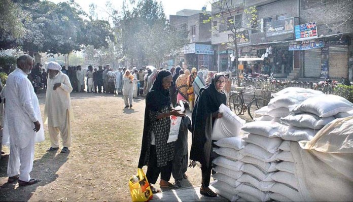 People standing in a queue to purchase wheat flour bags on government controlled rate at Istaqlalabad