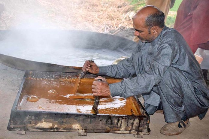 A farmer preparing traditional sweet item gur