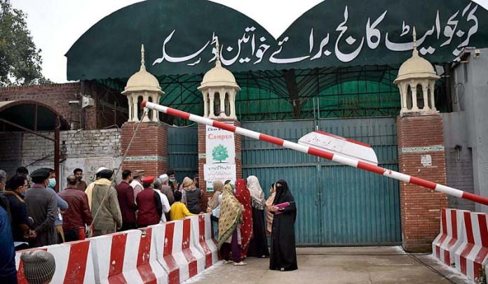 People waiting in long queue to cast their votes outside polling station in constituency NA-75, Sialkot-IV Daska