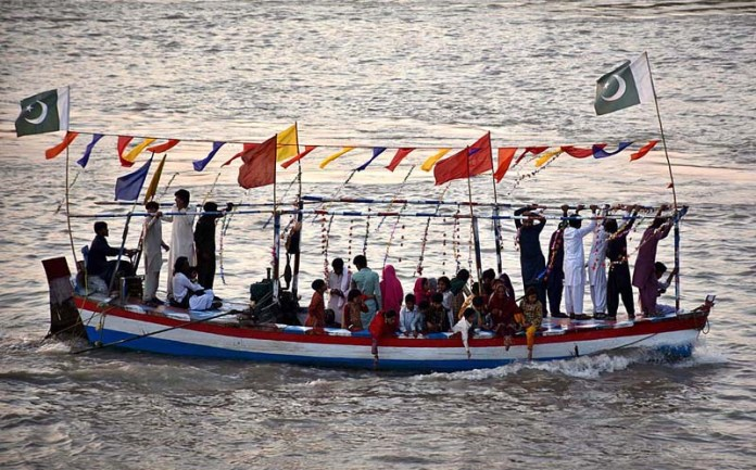 A large number of people enjoying a ride on boat in Indus River near Shaheed Mohtarma Benazir Bhutto Bridge