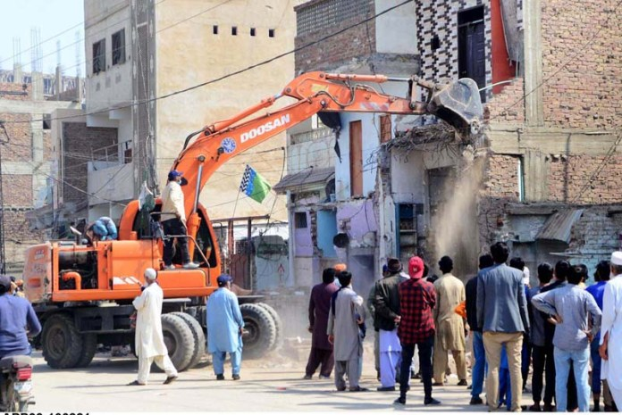 Workers of Anti Encroachment Cell of TMA demolishing encroachment with the help of heavy machinery at Bhitai Hospital Road