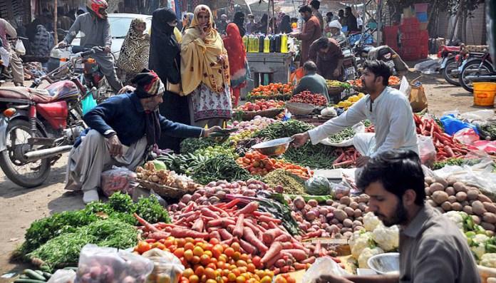 Customers purchasing vegetables from roadside vendor at Friday Bazaar