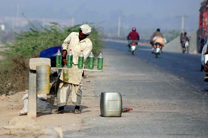 A vendor selling petrol illegally in plastic bottles at his roadside setup, needs the attention of concerned authorities