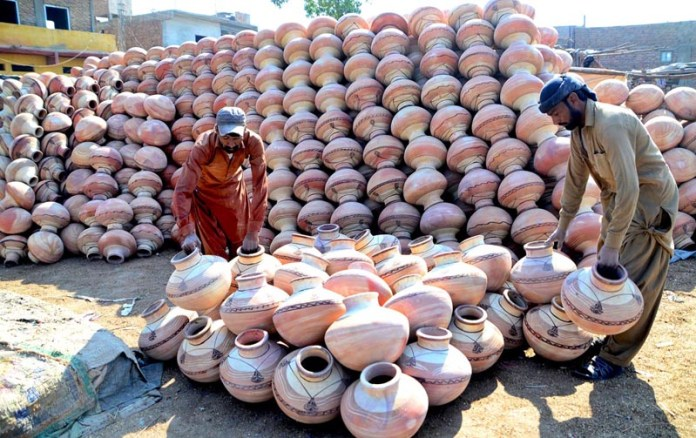 A vendor arranging the handmade clay pots to attract the customers at their workplace