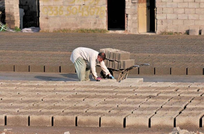 A labourer busy in arranging cemented blocks in a local factory at Baharakaho