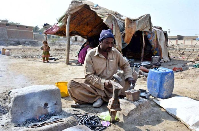 A worker busy in his work outside their makeshift houses at Ratodero