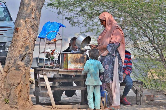 A women vendor preparing tea for customers at her roadside setup