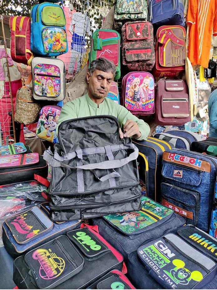 A vendor displaying and arranging bags at Shahi Bazaar to attract the customers