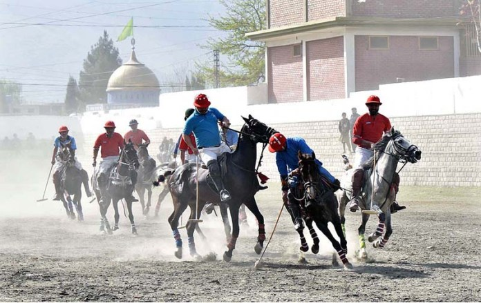 Players struggling to get hold on the ball in polo match played between NLI-A and NLI-B teams during Jashan-e-Baharan Polo Tournament at Shahi Polo Ground