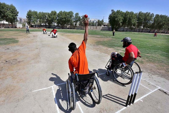 Players in action during 1st Pakistan Super Sixes Wheelchair Cricket Tournament 2021 organized by Pakistan Wheelchair Cricket Council (PWCC) at Degree College Ground