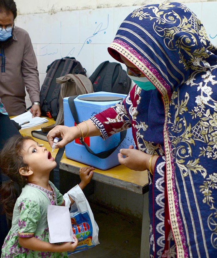 Lady health worker administering the polio drops to a child during 5 days anti-polio vaccination campaign at Bhitai Hospital