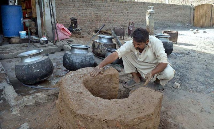 A worker giving final touches to traditional stove at his cooking workplace