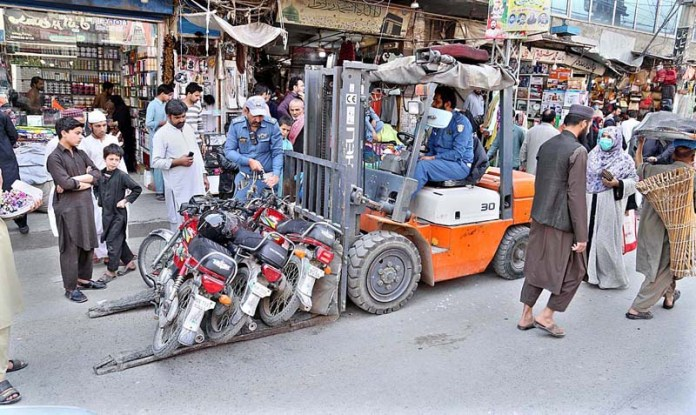 A warden of traffic police removing wrongly parked motorcycles in the city