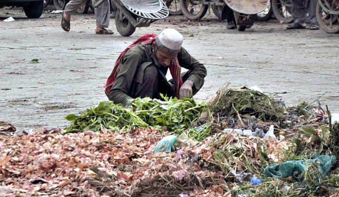 A gypsy searching valuables from heap of garbage in Vegetable Market
