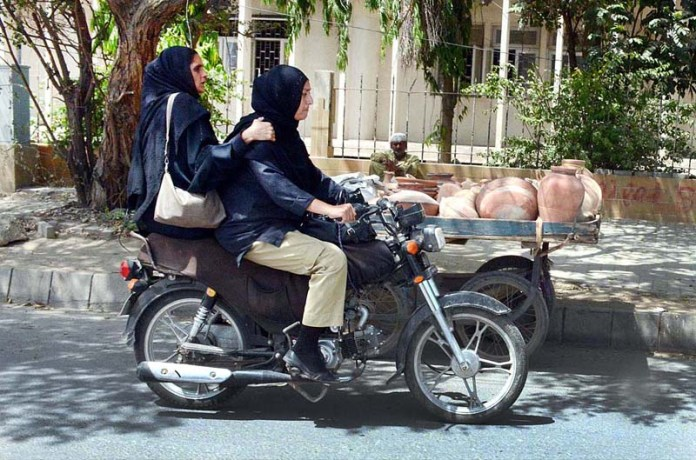 Women police official on their way on motorbike at I. I. Chudrigar Road in Provincial Capital