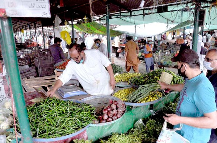 A large number of people busy in purchasing vegetables at Sunday Bazaar