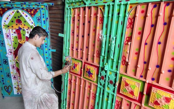 A worker busy in coloring on the Iron Gate at his workplace