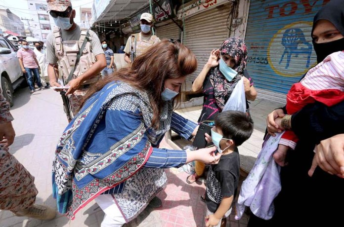 Assistant Commissioner, Saima Fatima wearing mask to a child during her visit at Latifabad market for implementation of lockdown as Sindh government announcement 6am to 2pm lockdown in the big markets as precautionary measures for COVID-19
