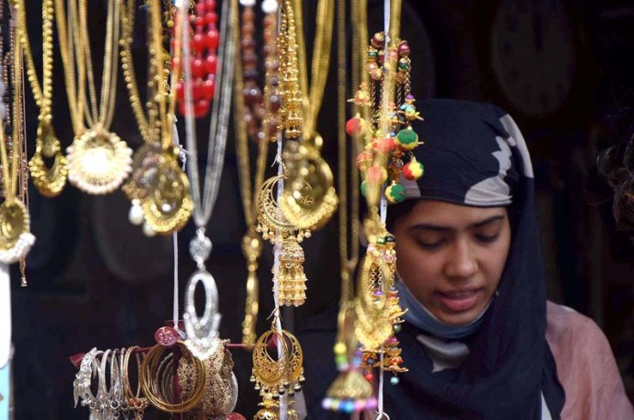A girl busy in shopping from jewelry stall ahead of the Eid-ul-Fitr at Kashmir Bazar