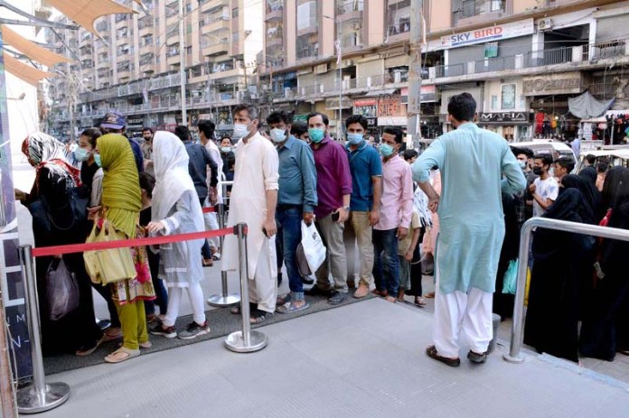 People standing in queue at the entrance gate of Atrium mall as a prevention measures taken by the mall management to contain spread of corona virus pandemic