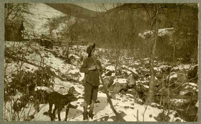 """The long rifle was in use in Appalachian Kentucky as late as 1904, as this photo shows. Back reads: """"John D. Bush, 12 years of age, squirrel hunting on Razor Fork of Clover Fork of Cumberland River. Young Bush carries a """"long rifle,"""" with double set trigger, as well as a powder horn and accompanied by a dog."""""""