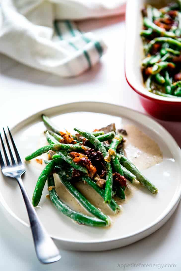 Keto Sautéed Green Beans with Bacon Cream Sauce on a white plate with fork and serving dish behind