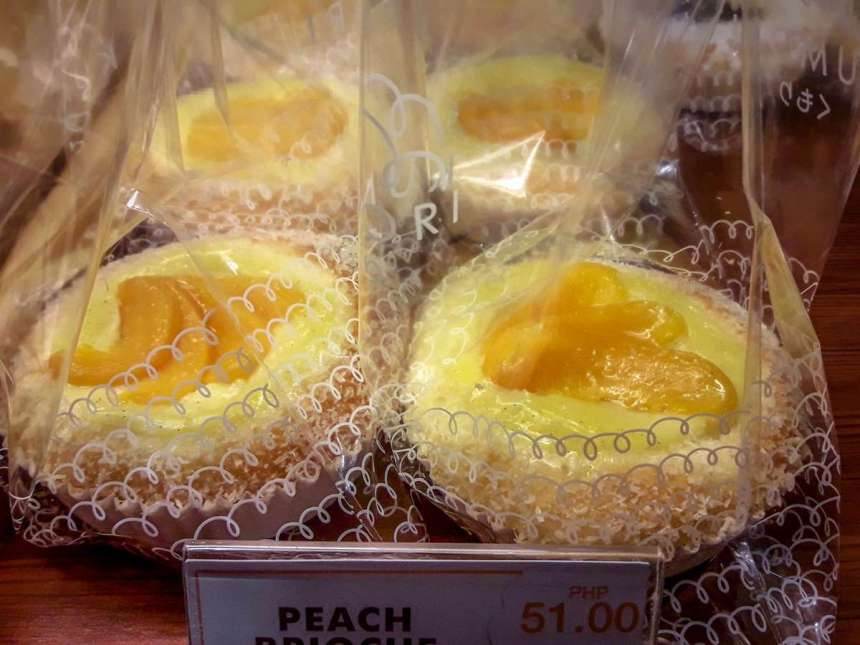 Peach Brioche Php51 Delicate premium brioche dough infused with a rich custard filling, topped with sliced sweet peaches, and a sprinkling of desiccated coconut