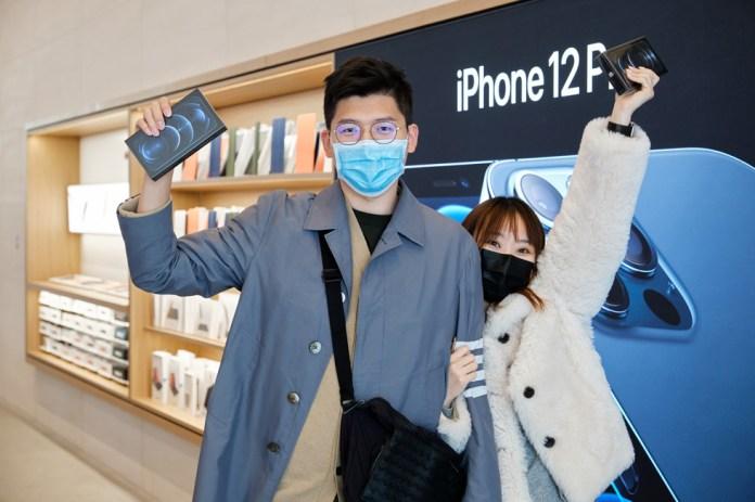 Due clienti di Apple Sanlitun mostrano con orgoglio i loro nuovi iPhone 12 Pro Max.
